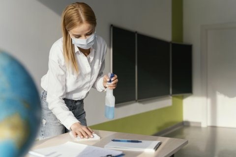 female-teacher-disinfecting-her-desk-classroom
